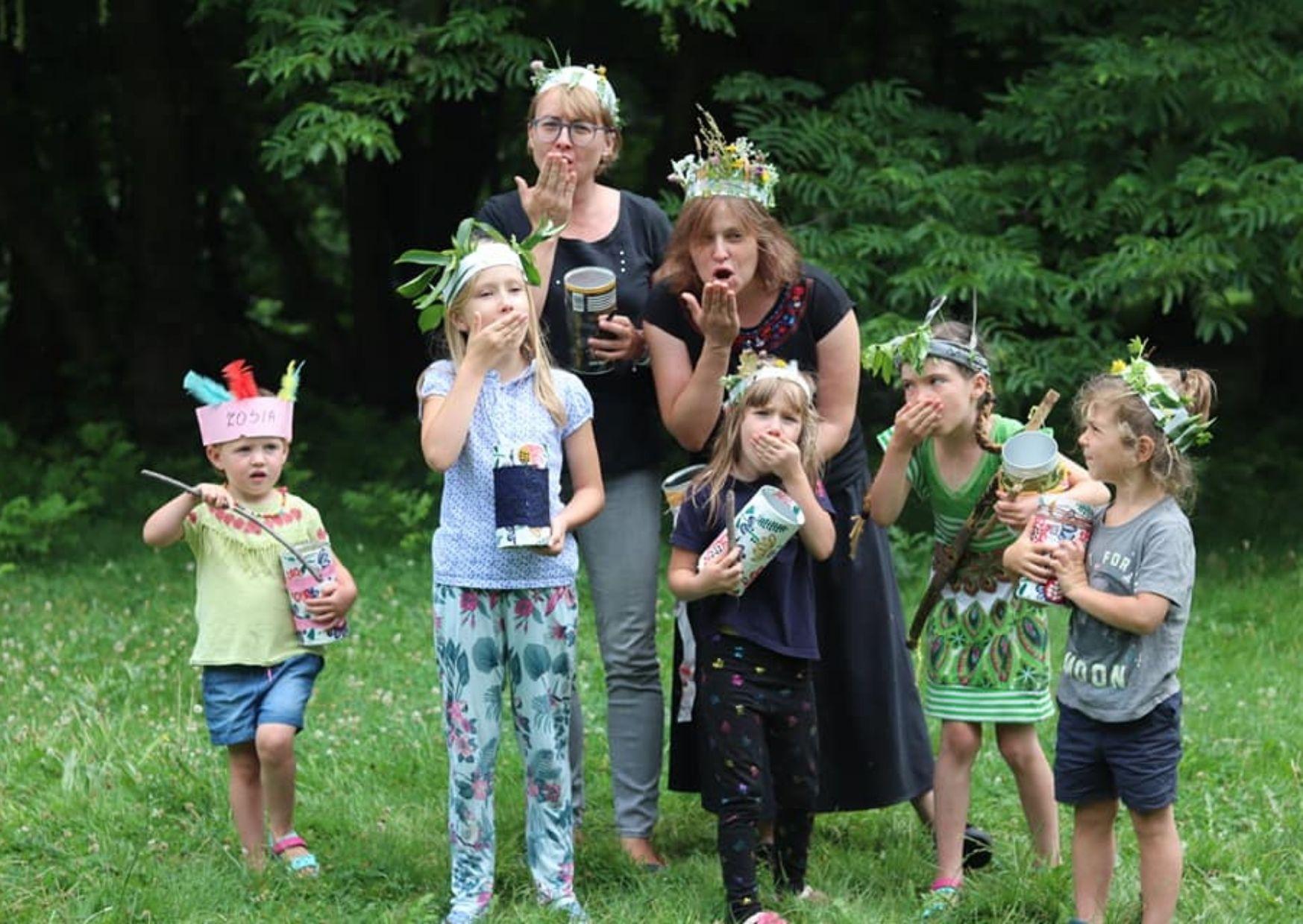 Na zdjęciu znajduje się grupa dzieci i osoby dorosłe w pióropuszach wykonanych z kartonu i roślin zielnych.