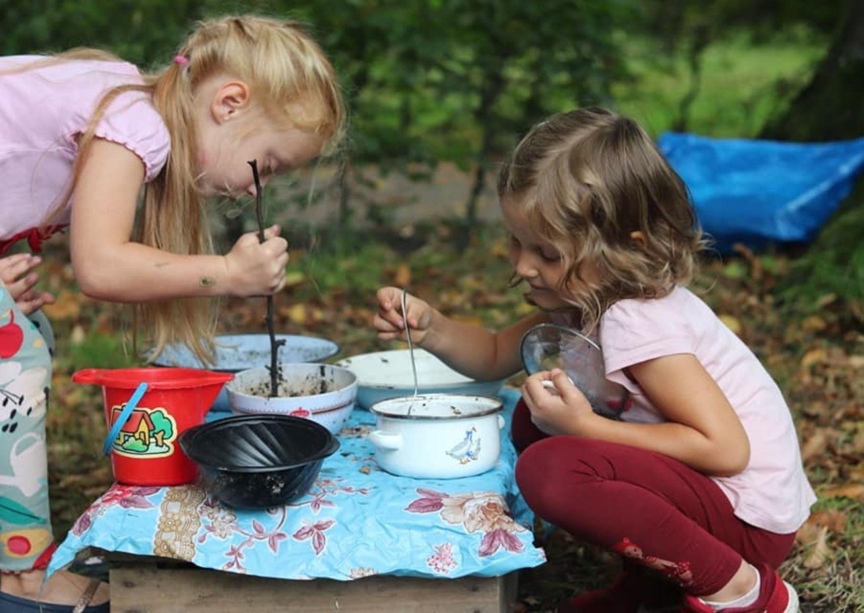 Dwie dziewczynki bawiące się w parku w gotowanie zupy z błota.
